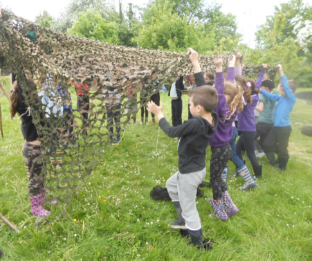 Children building a den - a large group of children holding up some netting