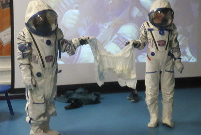Two children dressed in Space Suits in front of the screen