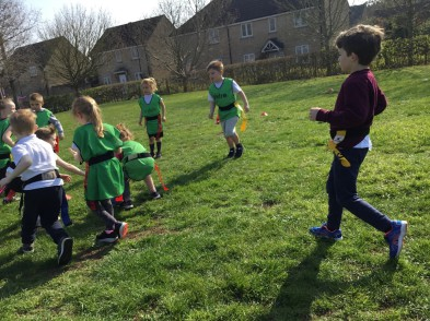 Year 1 at their Tag Rugby Tournament - 7 children running on the grass