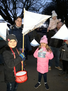 2 Fynamore children holding their lanterns with their parents behind