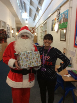 Mrs Zenanos with Father Christmas (holding a present) in the KS1 corridor